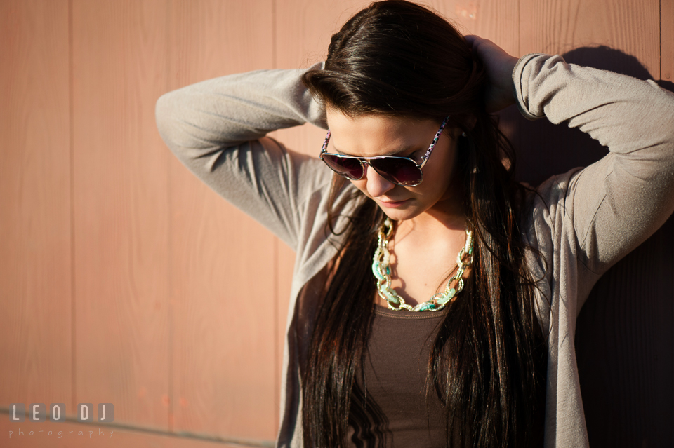 Brunette girl with sunglasses fixing her hair. Eastern Shore, Maryland, Queen Anne's County High School senior portrait session by photographer Leo Dj Photography. http://leodjphoto.com