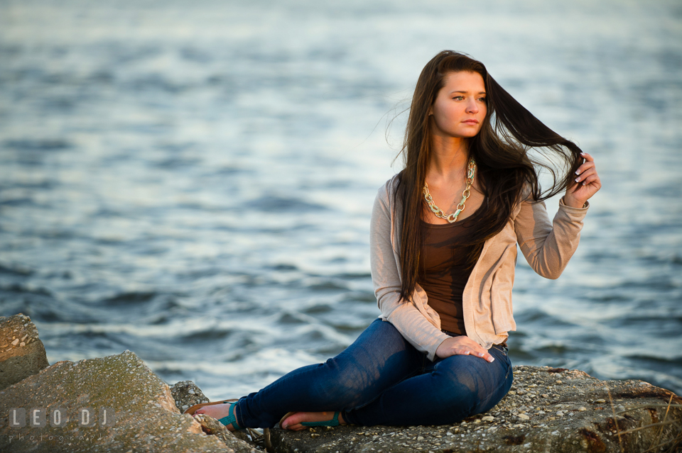 Beautiful brunette girl sitting on a rock by the water. Eastern Shore, Maryland, Queen Anne's County High School senior portrait session by photographer Leo Dj Photography. http://leodjphoto.com