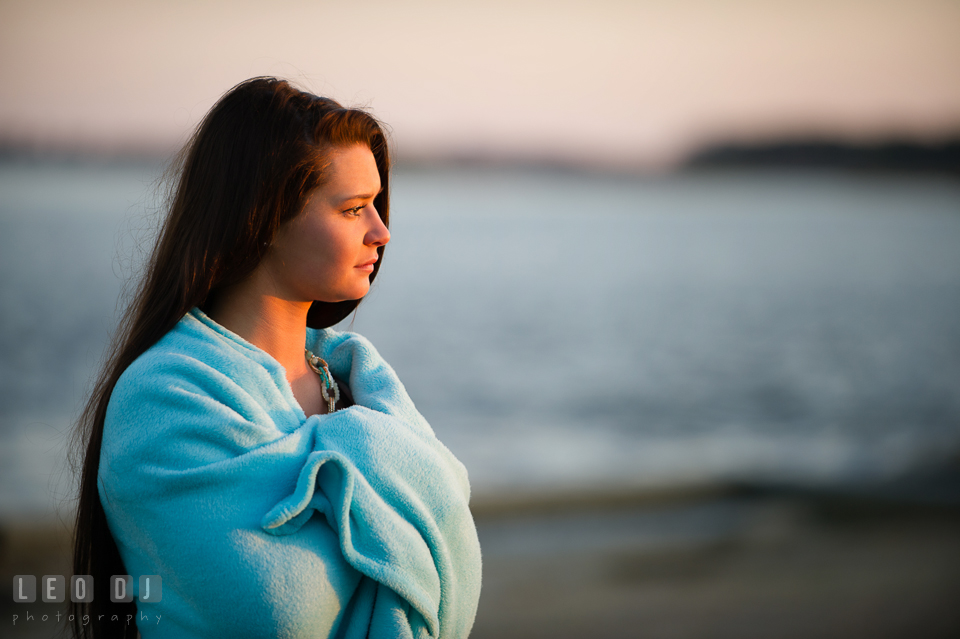 Beautiful brunette girl covered with blanket by the water looking at a distance. Eastern Shore, Maryland, Queen Anne's County High School senior portrait session by photographer Leo Dj Photography. http://leodjphoto.com