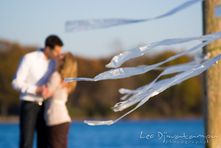 Engaged couple kissing in the background. Pre-wedding engagement photo session at Washington College and Chestertown, Maryland, by wedding photographer Leo Dj Photography.