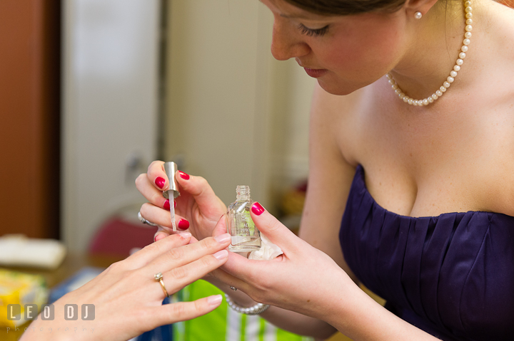 Bridesmaid help putting on nail polish on Bride's nails. St Andrews United Methodist wedding photos at Annapolis, Eastern Shore, Maryland by photographers of Leo Dj Photography.