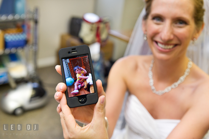 Bride showed picture on iPhone. St Andrews United Methodist wedding photos at Annapolis, Eastern Shore, Maryland by photographers of Leo Dj Photography.