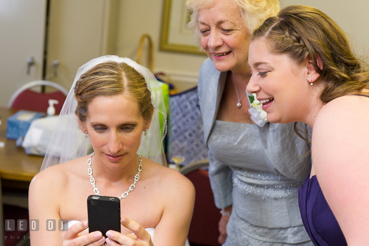 Bride, Mother of Bride and Bridesmaid smiling looking at picture on iPhone. St Andrews United Methodist wedding photos at Annapolis, Eastern Shore, Maryland by photographers of Leo Dj Photography.