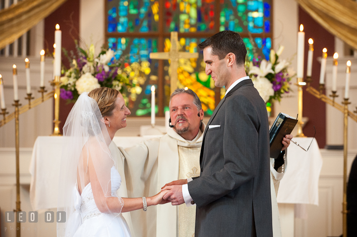 Bride and Groom smiled while blessed by the priest. St Andrews United Methodist wedding photos at Annapolis, Eastern Shore, Maryland by photographers of Leo Dj Photography.