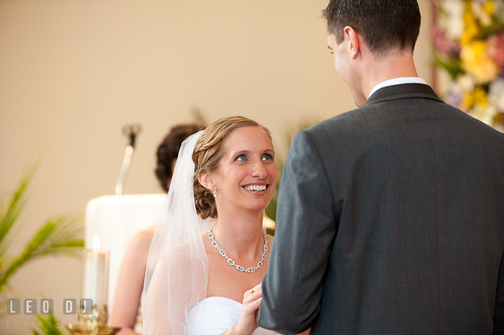 Bride smiled while putting on ring on Groom's finger. St Andrews United Methodist wedding photos at Annapolis, Eastern Shore, Maryland by photographers of Leo Dj Photography.