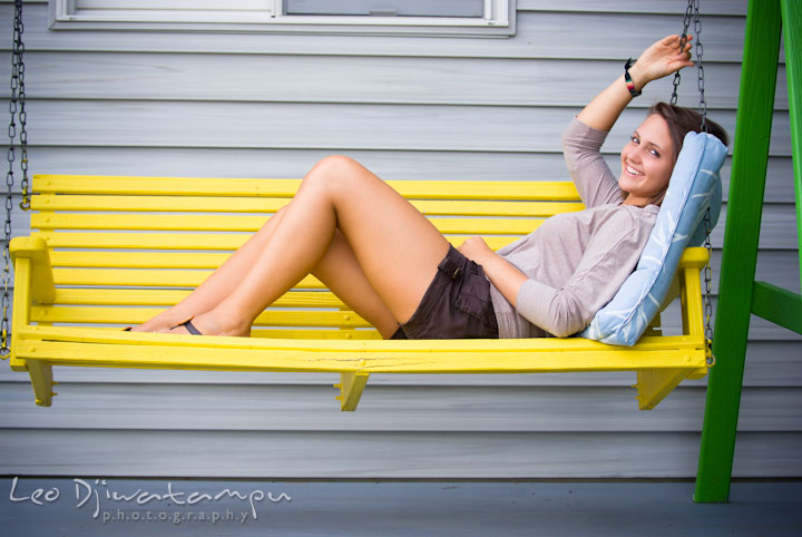 Girl lounging on yellow swing. Eastern Shore, Maryland, Kent Island High School senior portrait session by photographer Leo Dj Photography.
