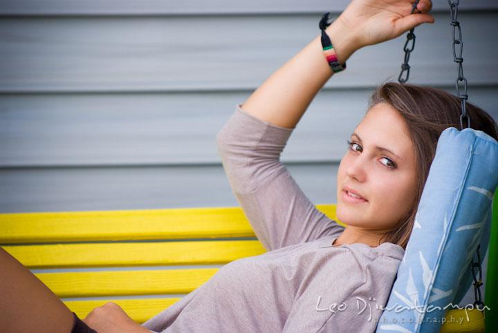 Girl sitting on yellow swing. Eastern Shore, Maryland, Kent Island High School senior portrait session by photographer Leo Dj Photography.