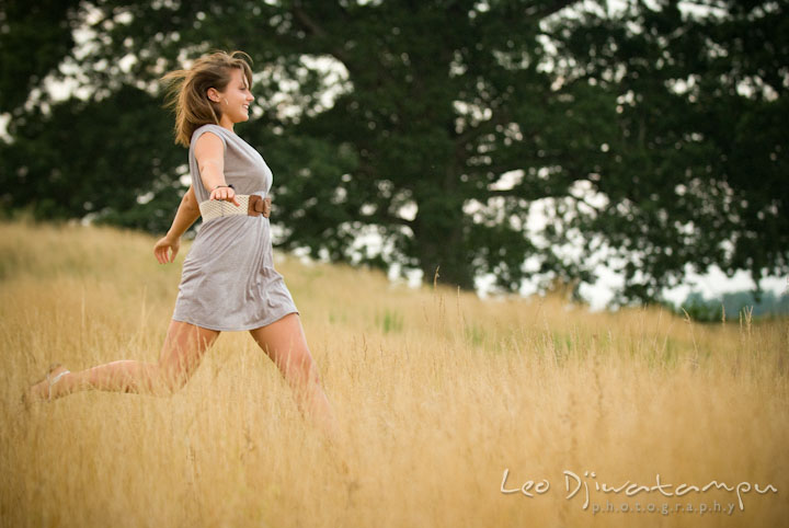 Girl running and jumping in the tall grass field. Eastern Shore, Maryland, Kent Island High School senior portrait session by photographer Leo Dj Photography.