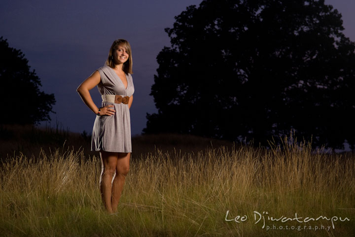 Girl posing in a grass field with evening sky. Eastern Shore, Maryland, Kent Island High School senior portrait session by photographer Leo Dj Photography.
