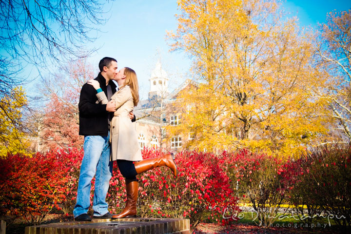 Engaged couple kissing in between yellow and red fall colored trees and bushes at campus. Chestertown Maryland and Washington College Pre-Wedding Engagement Session Photographer, Leo Dj Photography