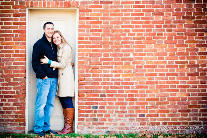 Engaged couple posing in front of a brick wall with a white door. Chestertown Maryland and Washington College Pre-Wedding Engagement Session Photographer, Leo Dj Photography