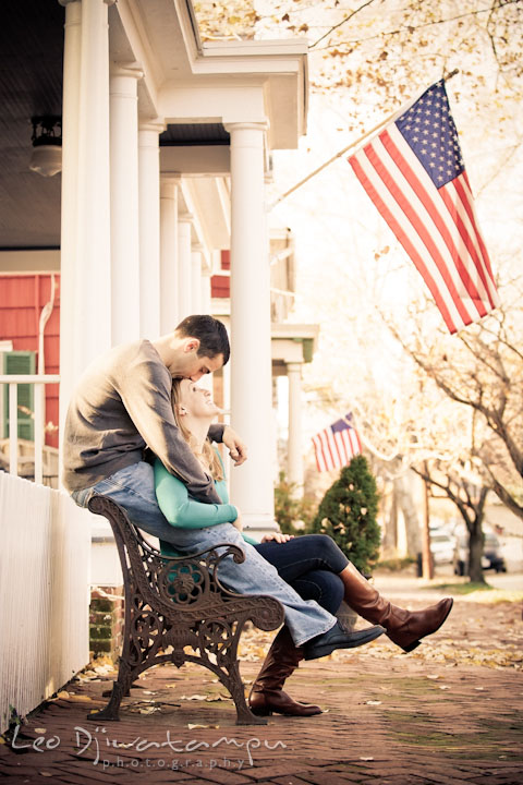 Engaged couple sitting on a bench. Fiancé kissed his fiancée's forehead. Chestertown Maryland and Washington College Pre-Wedding Engagement Session Photographer, Leo Dj Photography