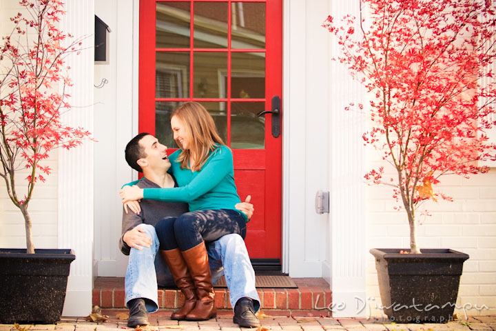 Engaged girl sitting on her fiancé's lap, in front of red door. Chestertown Maryland and Washington College Pre-Wedding Engagement Session Photographer, Leo Dj Photography