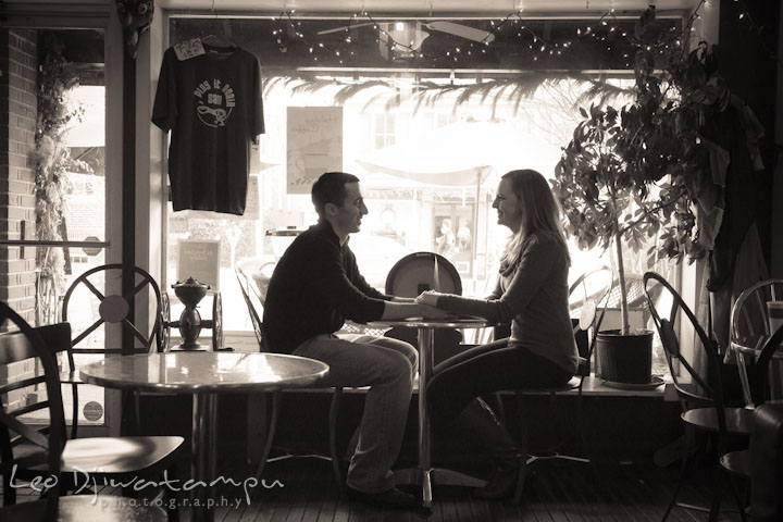 Engaged couple sitting inside coffee shop, holding hands. Chestertown Maryland and Washington College Pre-Wedding Engagement Session Photographer, Leo Dj Photography