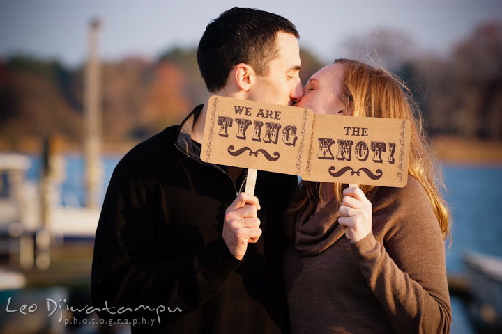 Fiancé and his fiancée kissing while holding we are tying the knot signs. Chestertown Maryland and Washington College Pre-Wedding Engagement Session Photographer, Leo Dj Photography