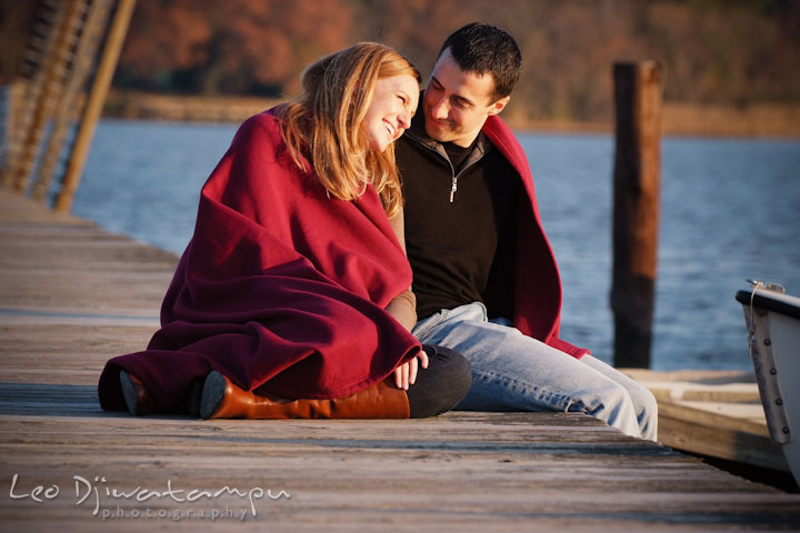Engaged couple sitting on a pier, smiling. Chestertown Maryland and Washington College Pre-Wedding Engagement Session Photographer, Leo Dj Photography