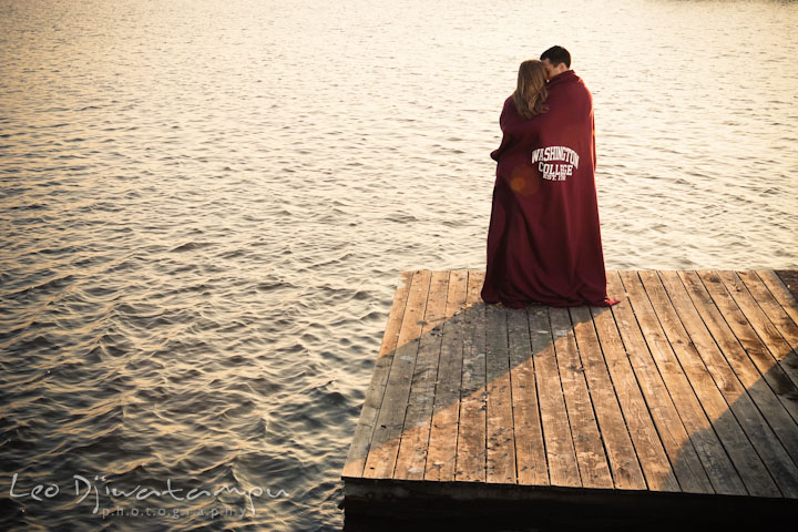 Fiancé and his fiancée cuddling on a pier with a college blanket. Chestertown Maryland and Washington College Pre-Wedding Engagement Session Photographer, Leo Dj Photography