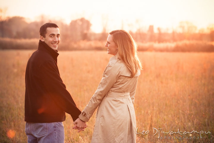 Engaged guy and girl in a meadow holding hands. Chestertown Maryland and Washington College Pre-Wedding Engagement Session Photographer, Leo Dj Photography