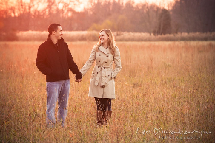 Engaged girl holding hands and looking at her fiancé in a meadow. Chestertown Maryland and Washington College Pre-Wedding Engagement Session Photographer, Leo Dj Photography