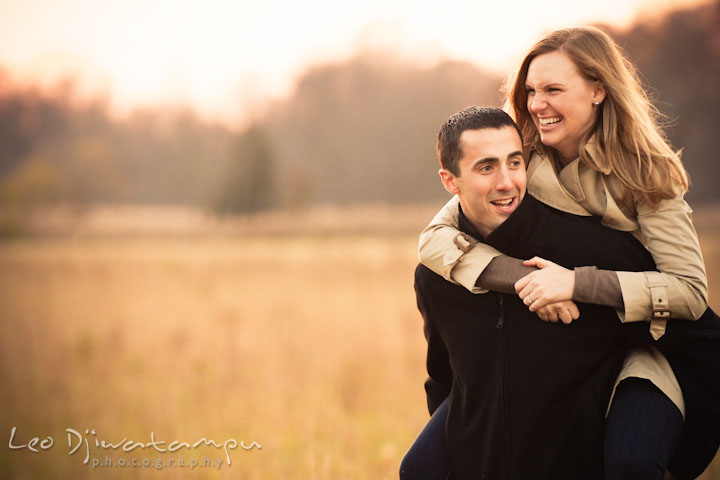 Engaged girl riding on fiancé's back, laughing. Chestertown Maryland and Washington College Pre-Wedding Engagement Session Photographer, Leo Dj Photography