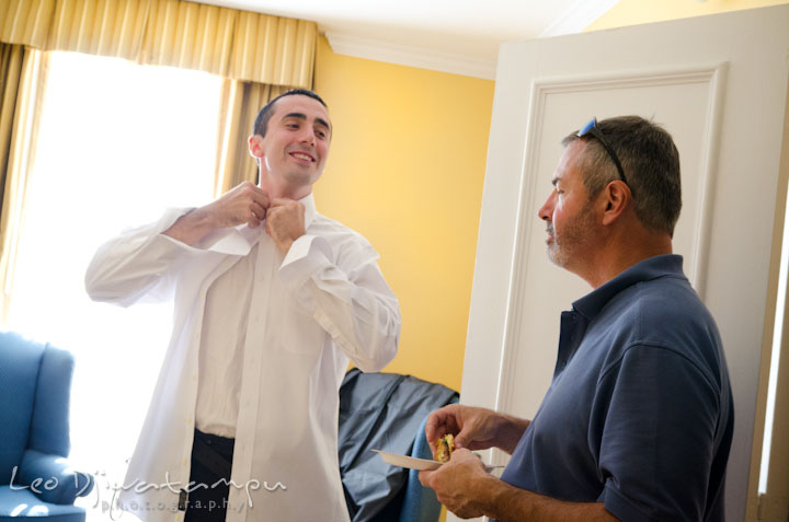 Groom putting on shirt. The Tidewater Inn Wedding, Easton Maryland, getting ready photo coverage of Kelsey and Jonnie by wedding photographers of Leo Dj Photography.