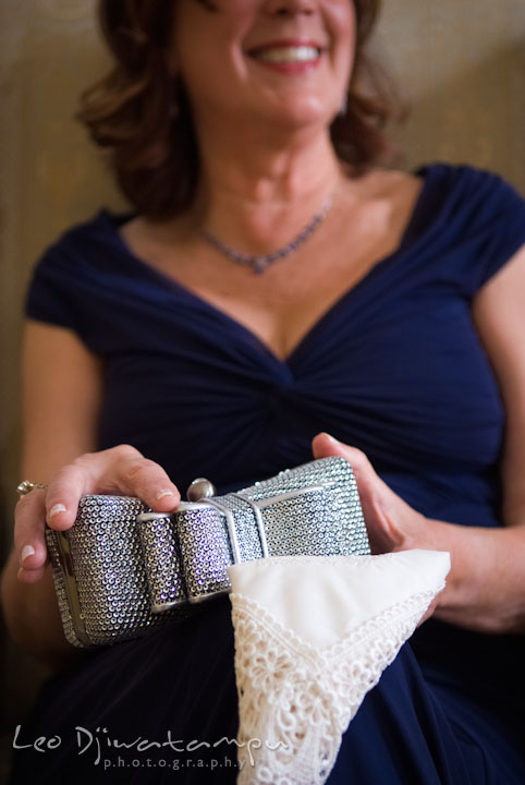 Mother of the bride holding purse and custom embroidered handkerchief. The Tidewater Inn Wedding, Easton Maryland, getting ready photo coverage of Kelsey and Jonnie by wedding photographers of Leo Dj Photography.