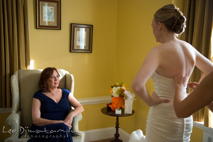 Mother of bride watching her daughter getting help for buttoning up her dress. The Tidewater Inn Wedding, Easton Maryland, getting ready photo coverage of Kelsey and Jonnie by wedding photographers of Leo Dj Photography.