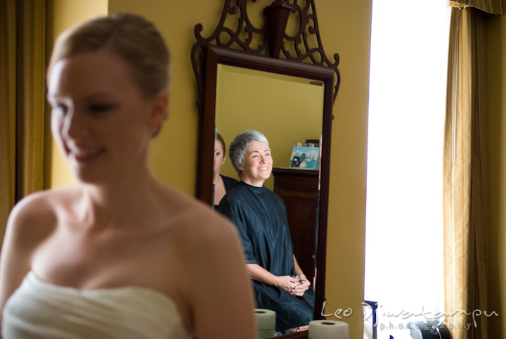 Mother of groom's reflection on mirror while watching bride putting on her dress. The Tidewater Inn Wedding, Easton Maryland, getting ready photo coverage of Kelsey and Jonnie by wedding photographers of Leo Dj Photography.