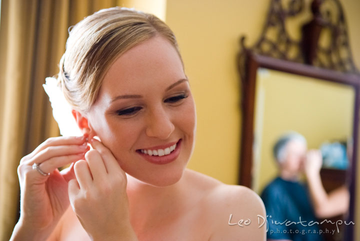 Bride putting on her earrings. The Tidewater Inn Wedding, Easton Maryland, getting ready photo coverage of Kelsey and Jonnie by wedding photographers of Leo Dj Photography.