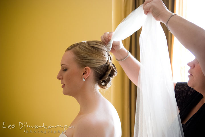 Bride getting help putting on veil. The Tidewater Inn Wedding, Easton Maryland, getting ready photo coverage of Kelsey and Jonnie by wedding photographers of Leo Dj Photography.