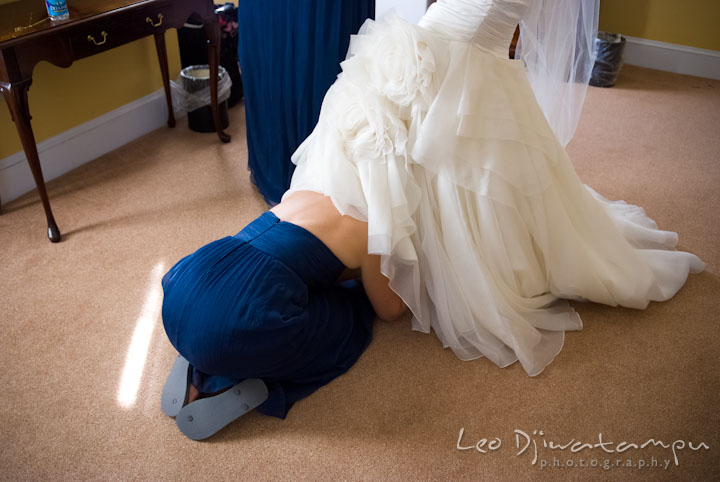 Maid of honor snuck under bride's dress to put shoes. The Tidewater Inn Wedding, Easton Maryland, getting ready photo coverage of Kelsey and Jonnie by wedding photographers of Leo Dj Photography.