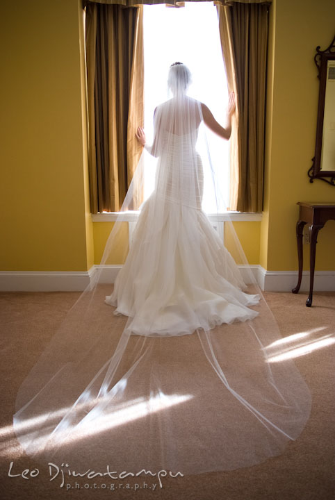 Bride posing by the window showing her long veil. The Tidewater Inn Wedding, Easton Maryland, getting ready photo coverage of Kelsey and Jonnie by wedding photographers of Leo Dj Photography.