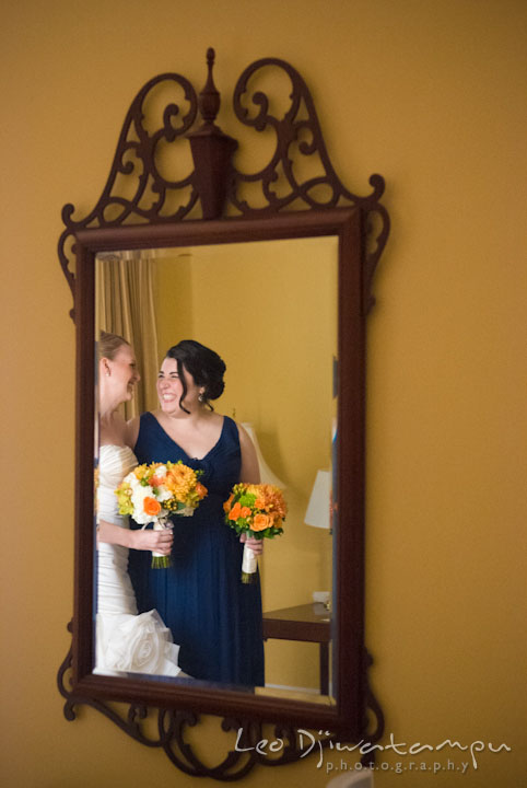 Reflection of bride and maid of honor laughing in the mirror. The Tidewater Inn Wedding, Easton Maryland, getting ready photo coverage of Kelsey and Jonnie by wedding photographers of Leo Dj Photography.