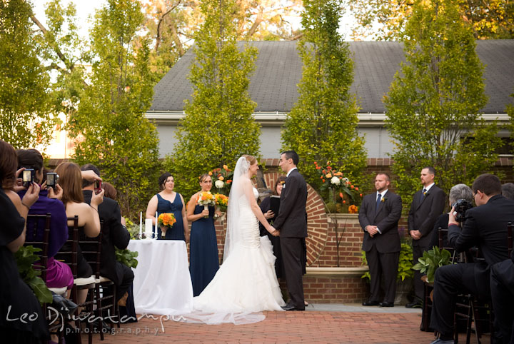 Bride and groom holding hand. The Tidewater Inn Wedding, Easton Maryland, ceremony photo coverage of Kelsey and Jonnie by wedding photographers of Leo Dj Photography.