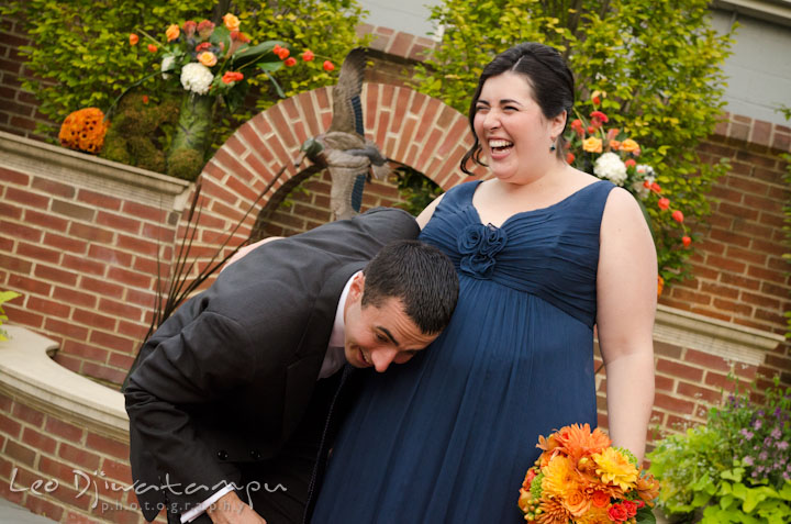 Groom listening to pregnant sister's belly. The Tidewater Inn Wedding, Easton Maryland, ceremony photo coverage of Kelsey and Jonnie by wedding photographers of Leo Dj Photography.