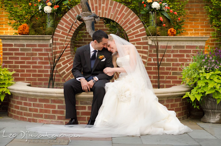 Bride and groom cuddling by the water fountain. The Tidewater Inn Wedding, Easton Maryland, ceremony photo coverage of Kelsey and Jonnie by wedding photographers of Leo Dj Photography.