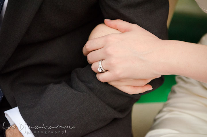 Bride's hand holding groom's arm and showing engagement ring and wedding band. The Tidewater Inn Wedding, Easton Maryland, ceremony photo coverage of Kelsey and Jonnie by wedding photographers of Leo Dj Photography.