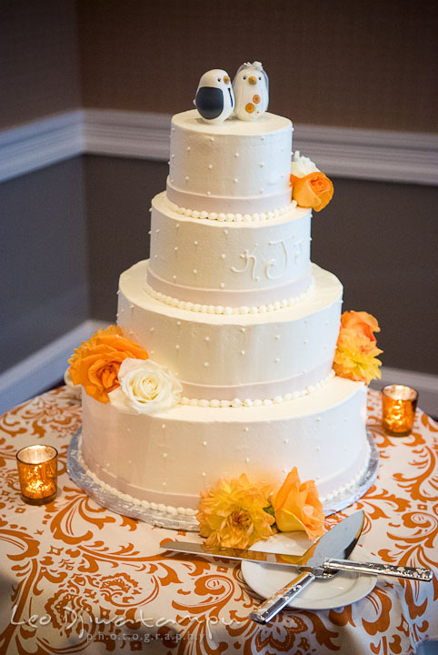 Four tier wedding cake with orange flowers. The Tidewater Inn Wedding, Easton Maryland, reception photo coverage of Kelsey and Jonnie by wedding photographers of Leo Dj Photography.