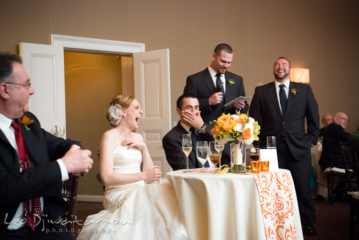 Bride and groom laughing while Best Man delivered speech. The Tidewater Inn Wedding, Easton Maryland, reception photo coverage of Kelsey and Jonnie by wedding photographers of Leo Dj Photography.
