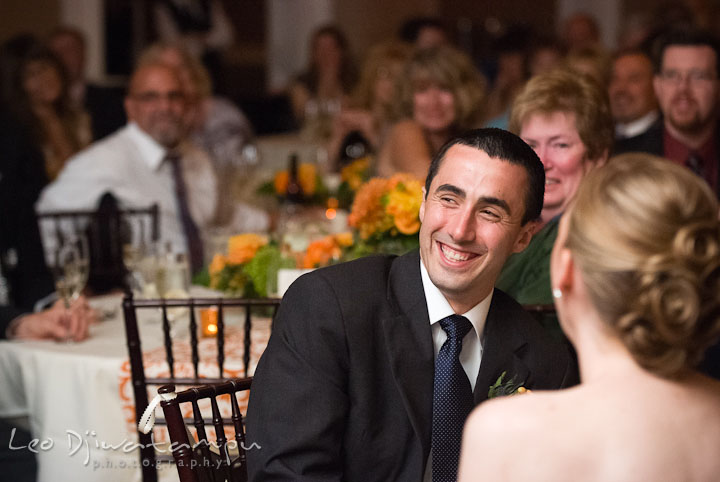 Groom laughing during matron of honor's speech. The Tidewater Inn Wedding, Easton Maryland, reception photo coverage of Kelsey and Jonnie by wedding photographers of Leo Dj Photography.