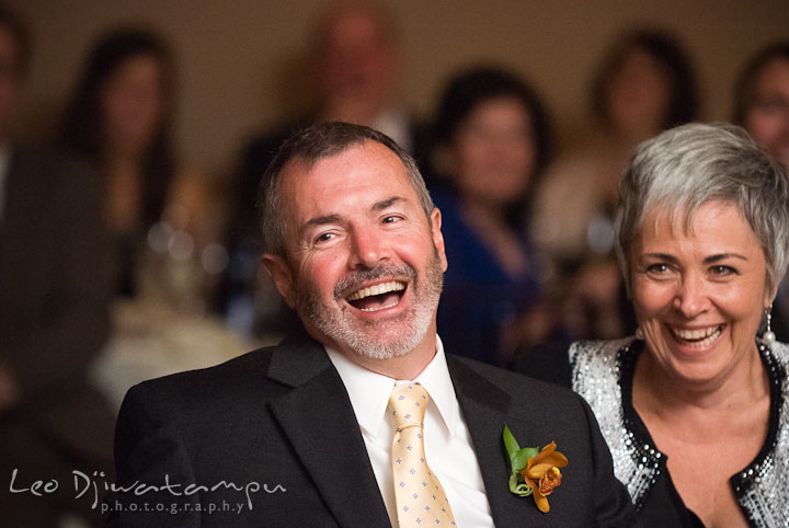 Father and mother of groom laughing during maid of honor's speech. The Tidewater Inn Wedding, Easton Maryland, reception photo coverage of Kelsey and Jonnie by wedding photographers of Leo Dj Photography.