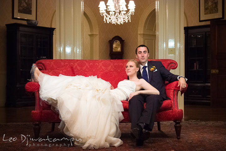 Bride and groom posing on a red antique sofa. The Tidewater Inn Wedding, Easton Maryland, reception photo coverage of Kelsey and Jonnie by wedding photographers of Leo Dj Photography.