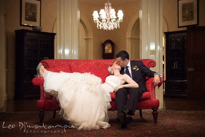 Bride and groom kissing on red antique sofa. The Tidewater Inn Wedding, Easton Maryland, reception photo coverage of Kelsey and Jonnie by wedding photographers of Leo Dj Photography.