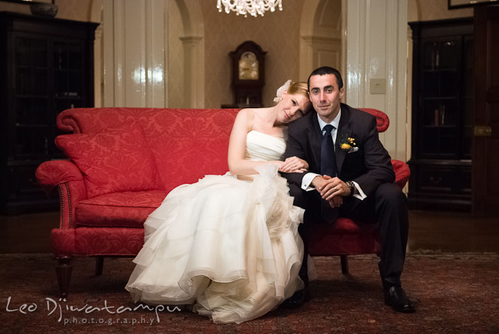 Bride sitting on red antique couch and leaning on groom's shoulder. The Tidewater Inn Wedding, Easton Maryland, reception photo coverage of Kelsey and Jonnie by wedding photographers of Leo Dj Photography.