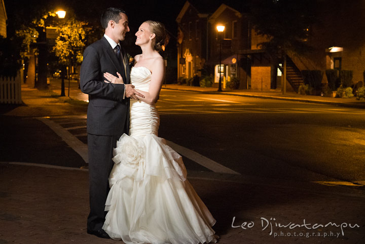 Bride and groom holding each other with city lights in the background. The Tidewater Inn Wedding, Easton Maryland, reception photo coverage of Kelsey and Jonnie by wedding photographers of Leo Dj Photography.