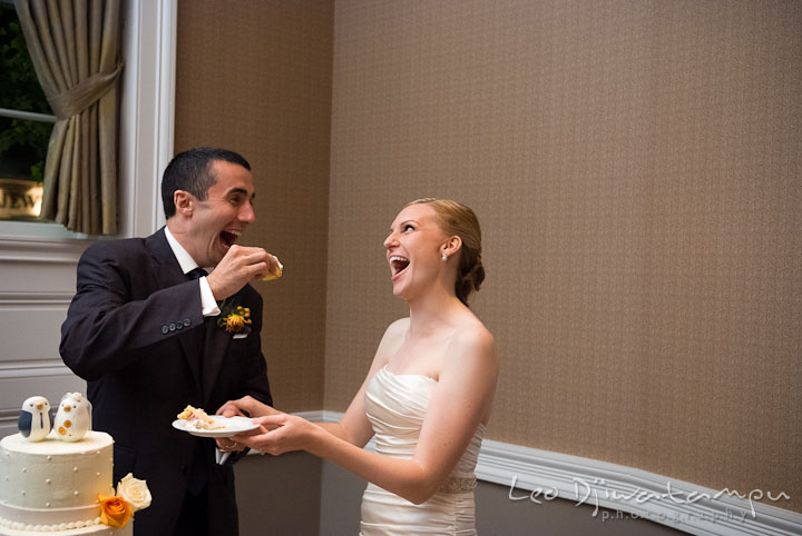 Bride and groom laughing while feeding each other wedding cake. The Tidewater Inn Wedding, Easton Maryland, reception photo coverage of Kelsey and Jonnie by wedding photographers of Leo Dj Photography.
