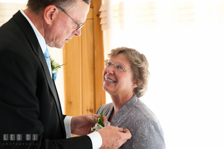 Father of the Bride putting on boutonniere on Mother of the Bride. Riverhouse Pavilion wedding photos at Easton, Eastern Shore, Maryland by photographers of Leo Dj Photography. http://leodjphoto.com