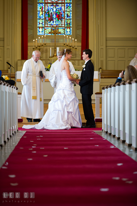 Bride and Groom holding hands, receiving prayers from the pastors. St. Mark United Methodist Church wedding photos at Easton, Eastern Shore, Maryland by photographers of Leo Dj Photography. http://leodjphoto.com