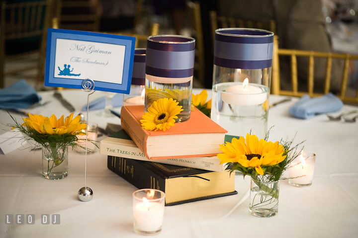 Table centerpiece decoration using books, candles, and flowers. Riverhouse Pavilion wedding photos at Easton, Eastern Shore, Maryland by photographers of Leo Dj Photography. http://leodjphoto.com