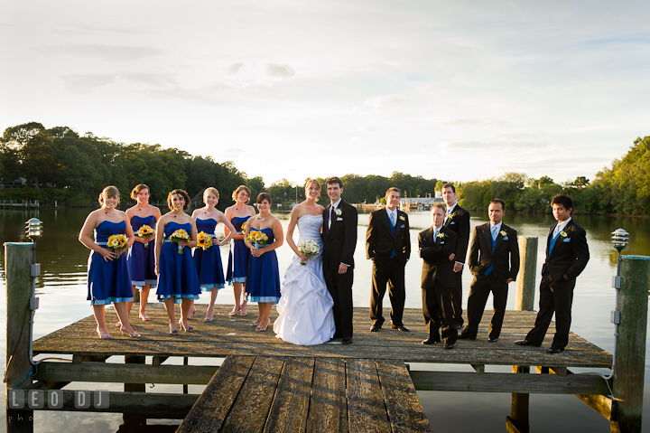 Bride and Groom posing with the wedding party at the boat pier. Riverhouse Pavilion wedding photos at Easton, Eastern Shore, Maryland by photographers of Leo Dj Photography. http://leodjphoto.com
